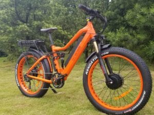 photo of an orange E-Cells electric bike on grass in front of trees